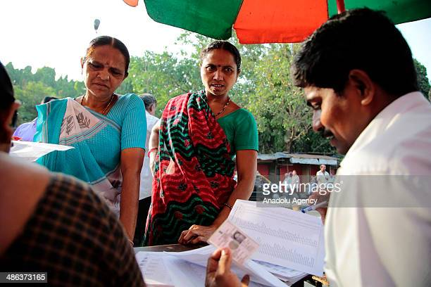 Indians check voter lists to confirm where they should cast their ballots during the sixth phase of the Indian parliamentary elections in Mumbai on...
