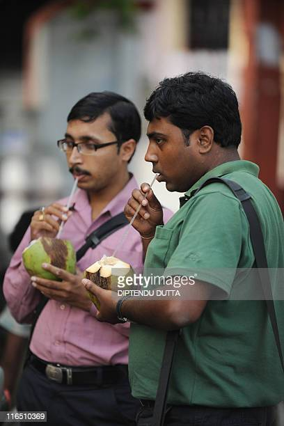 Indians drink coconut water at a roadside in Siliguri on May 262011 Coconut is in heavy demand during the summer months in India as people quench...