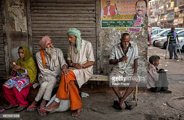 Indians drink tea under a poster showing BJP leader Narendra Modi at a chai stall on May 21 2014 in Delhi India India elected Hindu nationalist BJP...