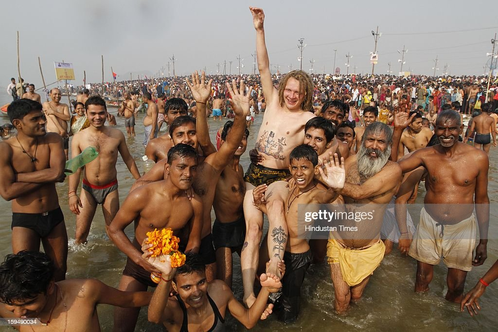Indians lifting foreigner devotee in air while taking first bath of Kumbh at the bank of Sangam confluence of river Ganga, Yamnuna and mythical Saraswati on the occasion of Makar Sankranti on January 14, 2013 in Allahabad, India. Kumbh is World's biggest religious gathering, in which more that 100 million of Hindus and sikh devotees will take part over next 55 days. Apart from being pilgrimage of faith, salvation and hope for millions of devotees, it also serve as meeting ground for the vast spectrum of Indian religious and spiritual views.