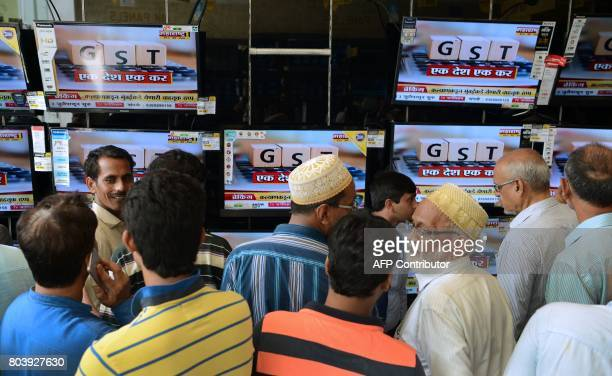 Indians look at televisions displaying news on the new Goods and Services Tax regime at an electronic appliances showroom in Mumbai on June 30 2017...