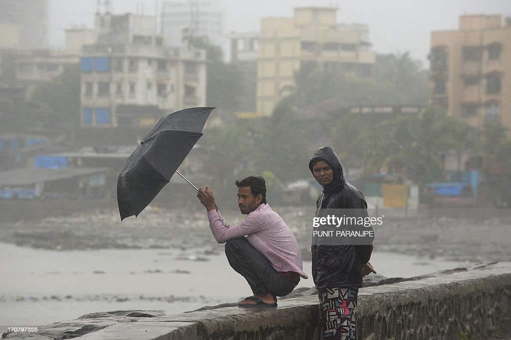 Indians look on by the sea front during heavy rain showers in Mumbai on June 18, 2013. The monsoon, which India's farming sector depends on, covers the subcontinent from June to September, usually bringing some flooding. But the heavy rains arrived early this year, catching many by surprise. The country has received 68 percent more rain than normal for this time of year, data from the India Meteorological Department shows.