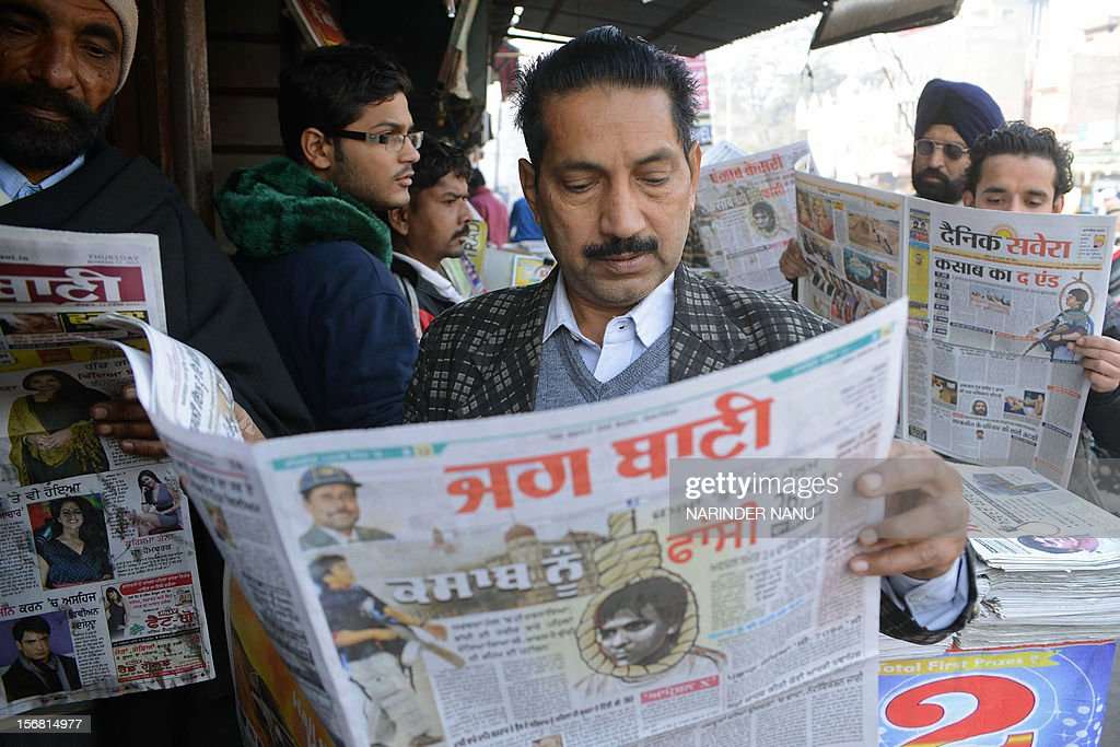Indians pose while reading newspapers displaying front page headlines on the execution of Mohammed Ajmal Amir Kasab who was the sole surviving gunman...