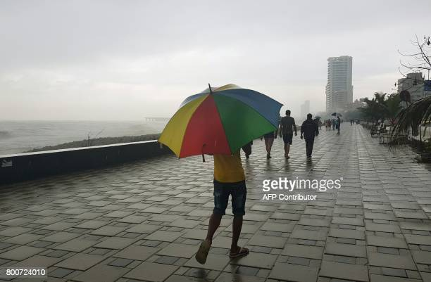 TOPSHOT Indians stroll along the sea front during monsoon showers in Mumbai on June 25 2017 PARANJPE
