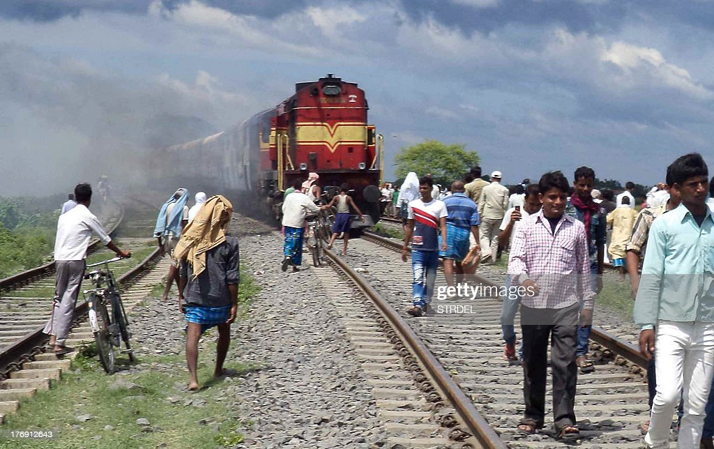 Indians walk on railroad tracks as train coaches of the Rajya Rani Express, set on fire by an angry mob, burns after the train ploughed into a crowd of Hindu pilgrims at the Dhamara Ghat railway station in Khagaria district, some 248 kilometres (154 miles) from Bihar state capital Patna, on August 19, 2013. An Indian express train ploughed into a crowd of Hindu pilgrims in the country's east on August 19, killing 37 and triggering a riot that left one of the drivers dead, an official said.