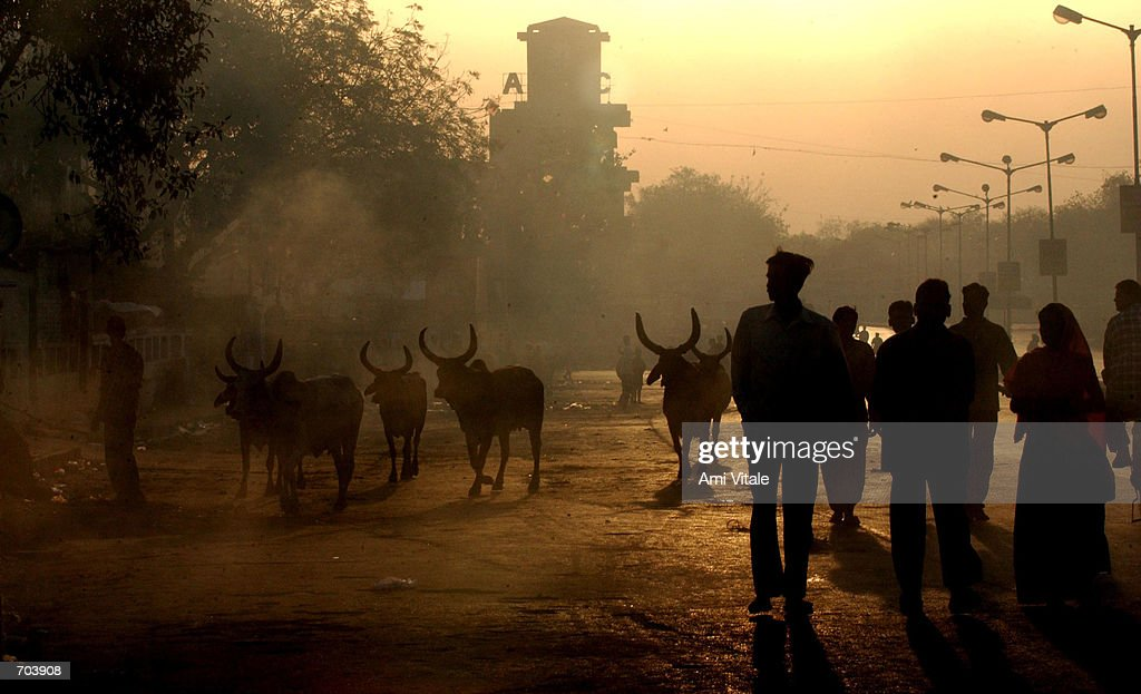 Indians walk through the smoky streets of Ahmadabad India March 1 2002 after a day of rioting Indian troops arrived in the riottorn western state of...