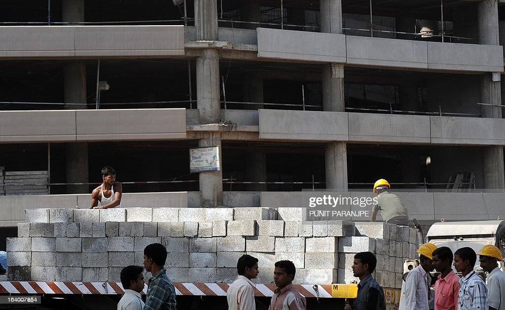 Indians workers shift blocks at a construction site near the international airport in Mumbai on March 19, 2013. India's central bank cut its main interest rate by 25 basis points on March 19, its second such reduction this year in an effort to jumpstart the slowing economy.