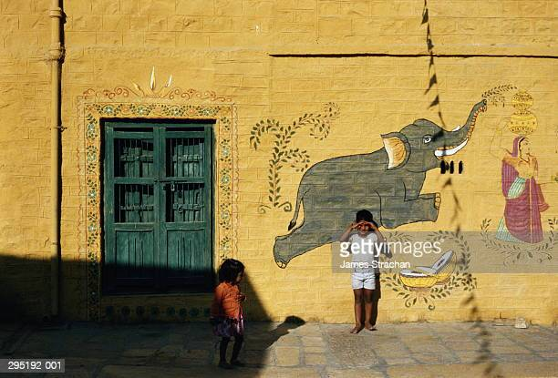 India,Rajasthan,Jaiselmer,murals on palace facade,children in front