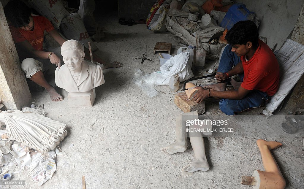 India-religion-society-art,FEATURE by Rachel O'Brien This photo taken on August 31, 2012 shows Indian carpenters working on statues at the Sequeira brothers' home and workshop in Small Giriz, some 70 kms north of Mumbai. For when a photograph is not enough, the Sequeiras -- a third-generation family of religious effigy makers -- operate a successful sideline to bereaved relatives who want a three-dimensional tribute to their lost loved ones. Using old photographs to capture a likeness, the statues and busts are made of wood or fibreglass, coloured with paint and completed with realistic glass eyes.