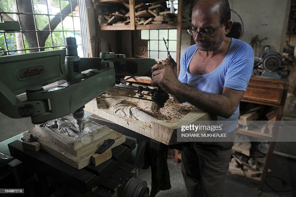 India-religion-society-art,FEATURE by Rachel O'Brien This photo taken on August 31, 2012 shows an Indian carpenter operating a wood carving duplicating machine to make a statue at the Sequeira brothers' home and workshop in Small Giriz, some 70 kms north of Mumbai. For when a photograph is not enough, the Sequeiras -- a third-generation family of religious effigy makers -- operate a successful sideline to bereaved relatives who want a three-dimensional tribute to their lost loved ones. Using old photographs to capture a likeness, the statues and busts are made of wood or fibreglass, coloured with paint and completed with realistic glass eyes.