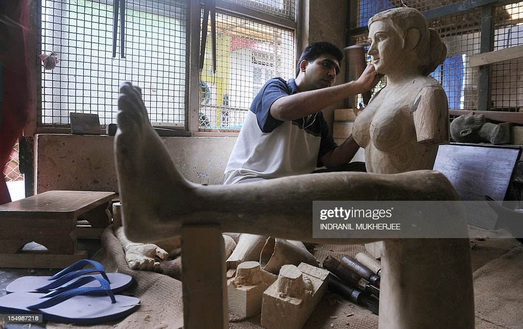 India-religion-society-art,FEATURE by Rachel O'Brien This photo taken on August 31, 2012 shows third generation Indian statue maker Benzony Sequeira working on an unfinished statue of Goddess Gauri at the Sequeira brothers' home and workshop in Small Giriz, some 70 kms north of Mumbai. For when a photograph is not enough, the Sequeiras -- a third-generation family of religious effigy makers -- operate a successful sideline to bereaved relatives who want a three-dimensional tribute to their lost loved ones. Using old photographs to capture a likeness, the statues and busts are made of wood or fibreglass, coloured with paint and completed with realistic glass eyes.