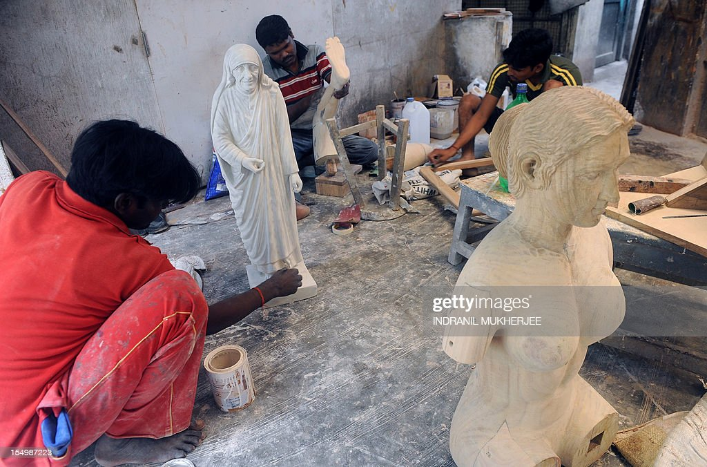 India-religion-society-art,FEATURE by Rachel O'Brien This photo taken on August 31, 2012 shows Indian carpenters working on statues at the Sequeira brothers' home and workshop in Small Giriz, some 70 kms north of Mumbai. For when a photograph is not enough, the Sequeiras -- a third-generation family of religious effigy makers -- operate a successful sideline to bereaved relatives who want a three-dimensional tribute to their lost loved ones. Using old photographs to capture a likeness, the statues and busts are made of wood or fibreglass, coloured with paint and completed with realistic glass eyes. AFP PHOTO / INDRANIL MUKHERJEE