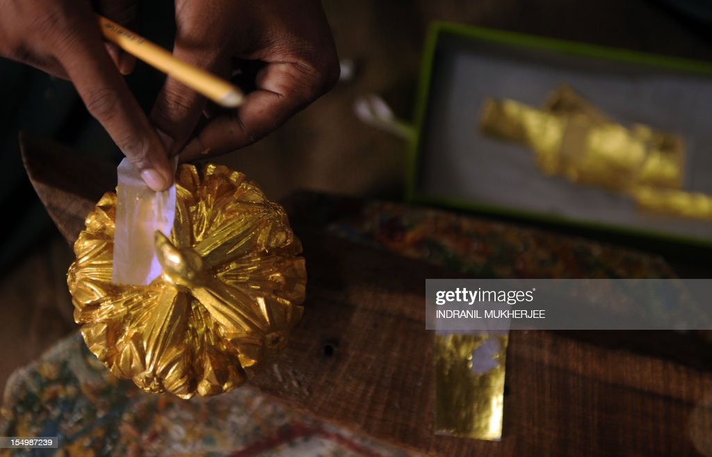 India-religion-society-art,FEATURE by Rachel O'Brien This photo taken on September 3, 2012 shows an Indian carpenter placing original gold leaf paint on a statue at the Sequeira brothers' home and workshop in Small Giriz, some 70 kms north of Mumbai. For when a photograph is not enough, the Sequeiras -- a third-generation family of religious effigy makers -- operate a successful sideline to bereaved relatives who want a three-dimensional tribute to their lost loved ones. Using old photographs to capture a likeness, the statues and busts are made of wood or fibreglass, coloured with paint and completed with realistic glass eyes. AFP PHOTO / INDRANIL MUKHERJEE