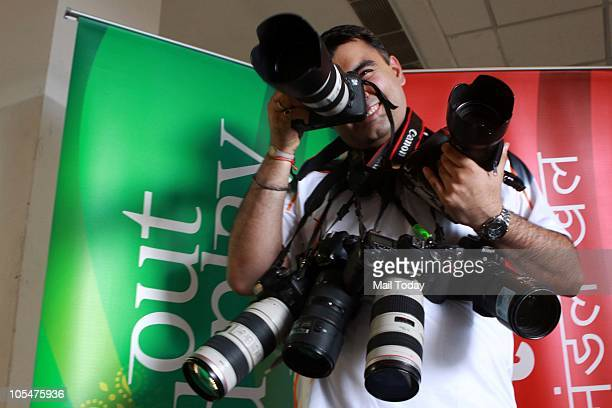 India's ace shooter Gagan Narang poses with cameras of photojournalists after the last shooting event of Commonwealth Games 2010 at Dr K Singh...