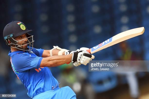 India's Ajinkya Rahane hits a boundary during the first One Day International match between West Indies and India at the Queen's Park Oval in Port of...