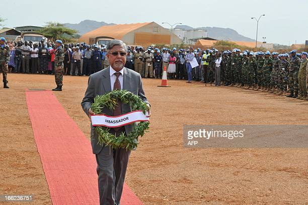 India's Ambassador to South Sudan Parmod Bajaj carries a wreath of flowers as he attends on April 10 in Juba a funeral ceremony for the five Indian...