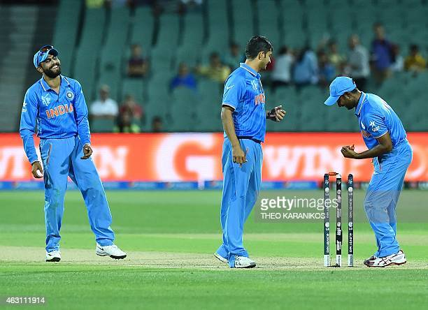 India's Ambati Rayudu runs out an Afghanistan batsman as Ravindra Jadeja and Mohit Sharma watch on during the oneday international World Cup warmup...