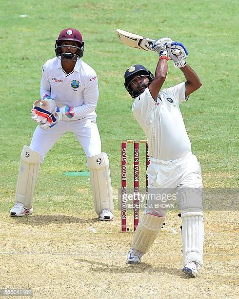 India's Amit Mishra and West Indies wicket keeper Shane Dowrich watch the hit for a Six off a delivery from West Indies bowler Devendra Bishoo on day...