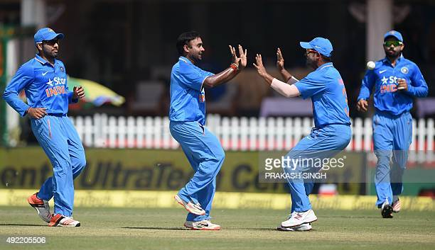 India's Amit Mishra celebrates with teammate Suresh Raina after bowling South Africa's Hashim Amla during the first one day international cricket...