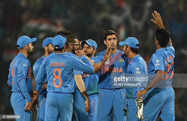 India's Ashish Nehra celebrates with teammates after taking the wicket of New Zealand batsman Colin Munro during the World T20 cricket tournament...