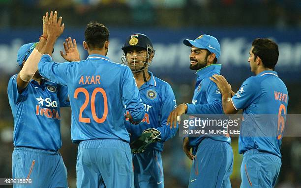 India's Axar Patel is congratulated by teammates for taking the wicket of South Africa's Faf du Plessis during the second one day international...