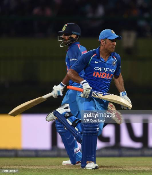 India's batsman MS Dhoni and Bhuvneshwar Kumar runs between the wickets during the second One Day International cricket match between Sri Lanka and...