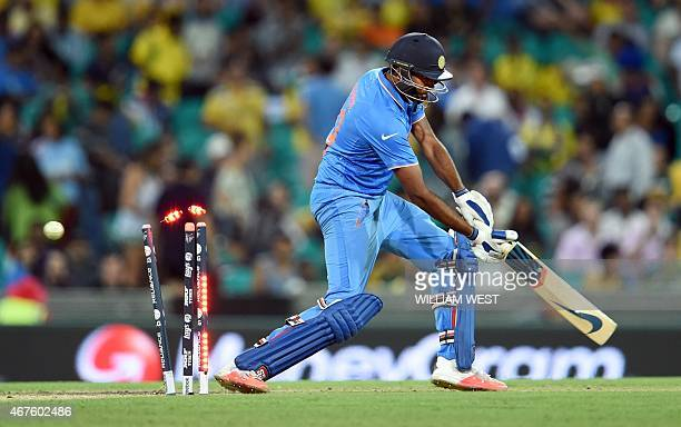 India's batsman Ravi Ashwin is bowled by Australia's James Faulkner during their 2015 Cricket World Cup semifinal match in Sydney on March 26 2015...