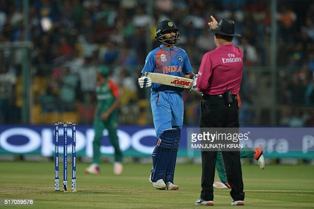 India's batsman Shikhar Dhawan walks back to the pavilion as the umpire gives an LBW out decision during the World T20 cricket tournament match...