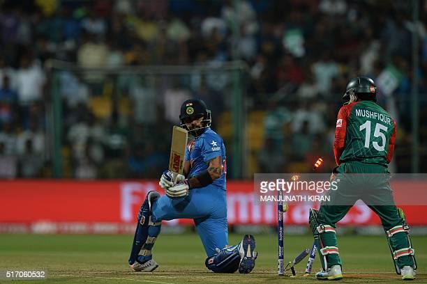 India's batsman Virat Kohli and Bangladesh wicketkeeper Mushfiqur Rahim look on as Kohli is bowled out for 24 runs during the World T20 cricket...