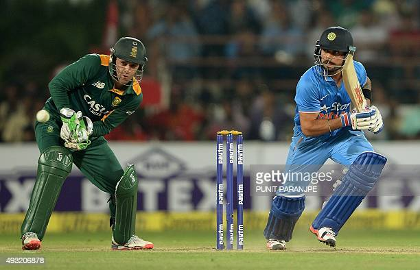 India's batsman Virat Kohli plays a shot as South Africa's captain and wicketkeeper AB de Villiers watches during the third one day international...