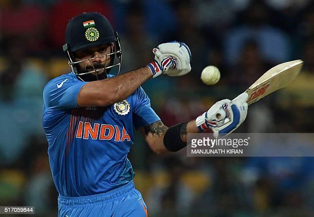 India's batsman Virat Kohli plays a shot during the World T20 cricket tournament match between India and Bangladesh at The Chinnaswamy Stadium in...