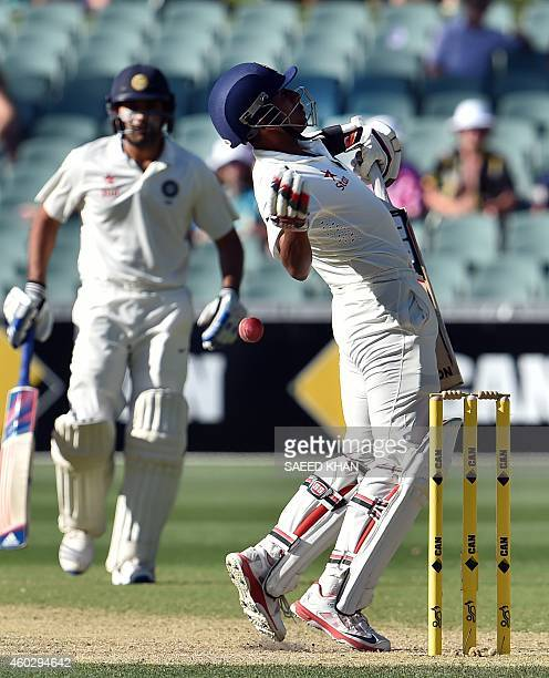 India's batsman Wriddhiman Saha is hit by a bouncer from Australia's Mitchell Johnson on the third day of the first Test cricket match between...