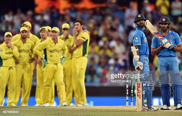 India's batsmen Rohit Sharma Shikhar Dhawan and Australia players wait for the third umpire's decision for the caught behind appeal during the...