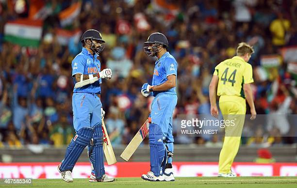 India's batsmen Shikhar Dhawan and Rohit Sharma chat after taking more runs from Australian bowler James Faulkner during their 2015 Cricket World Cup...