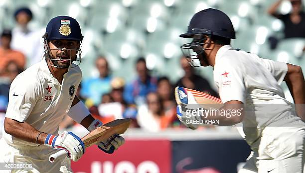 India's batsmen Virat Kohli and Rohit Sharma run between the wickets on the third day of the first Test cricket match between Australia and India at...