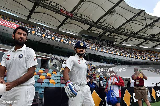 India's batting pair Virat Kohli and Cheteshwar Pujara walk onto the grounds on the fourth day of the 2nd cricket Test match between Australia and...
