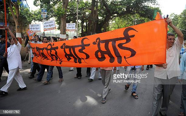 India's Bharatiya Janata Party supporters march with a proHindu solidarity banner that reads 'We all Hindus are brothers' during a protest rally...