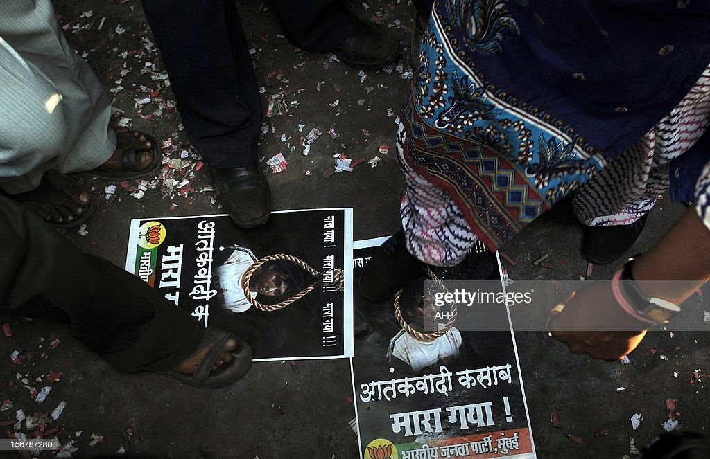 India's Bharatiya Janta Party activists step on posters of Pakistan-born Mohammed Kasab, the sole surviving gunman of the 2008 Mumbai attacks, as they celebrate Kasab's executiuon, in Mumbai on November 21, 2012. The sole surviving gunman from the 2008 Mumbai attacks was executed on November 21 to the relief of survivors and victims' families, nearly four years after 166 people died in the three-day rampage.
