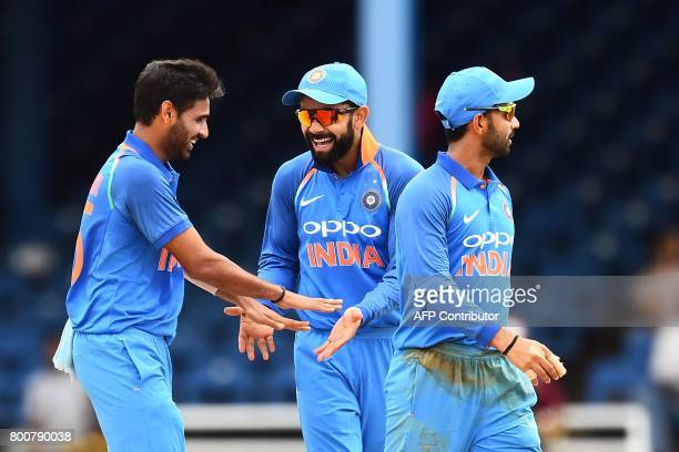 India's Bhuvneshwar Kumar celebrates with captain Virat Kohli and teammate Ajinkya Rahane after dismissing West Indies' Jason Mohammed during the...