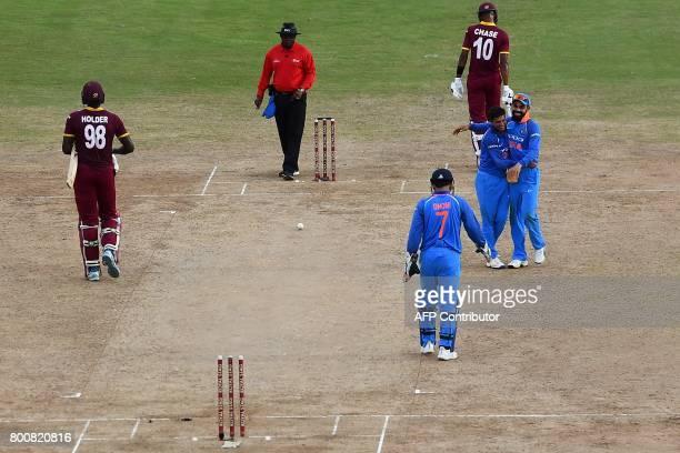 India's Bhuvneshwar Kumar celebrates with team captain Virat Kohli after dismissing West Indies' captain Jason Holder during the second One Day...
