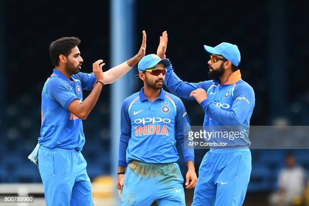 India's Bhuvneshwar Kumar celebrates with teammate Ajinkya Rahane and captain Virat Kohli after dismissing West Indies' Jason Mohammed during the...