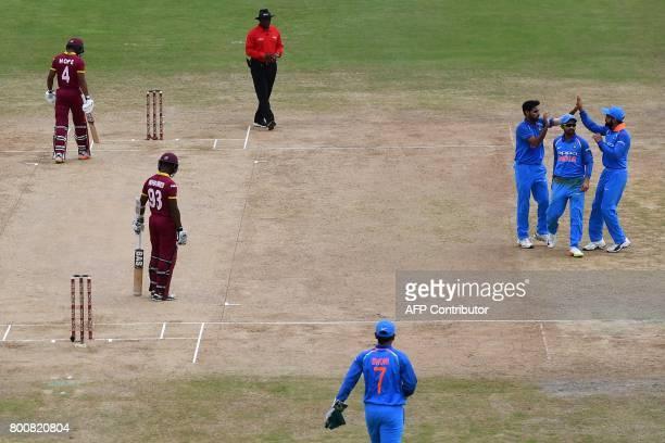 India's Bhuvneshwar Kumar celebrates with teammate Ajinkya Rahane and captain Virat Kohli after dismissing West Indies' Jason Mohammed during the...