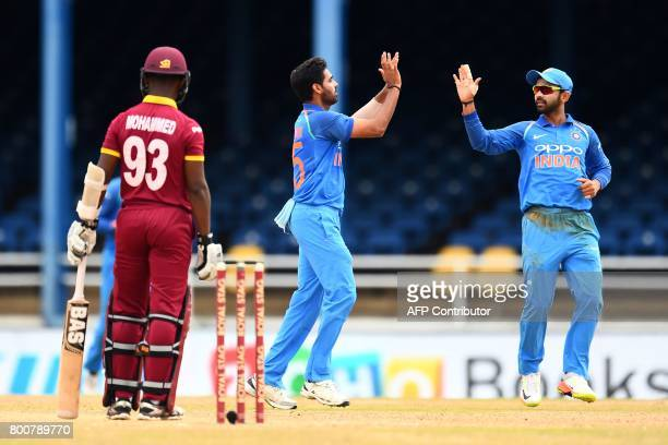 India's Bhuvneshwar Kumar celebrates with teammate Ajinkya Rahane after dismissing West Indies' Jason Mohammed during the second One Day...