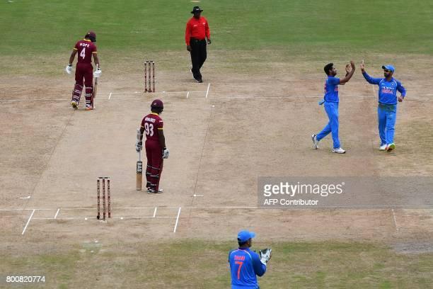 India's Bhuvneshwar Kumar celebrates with teammate Ajinkya Rahane after dismissing West Indies' Jason Mohammed during the second One Day...