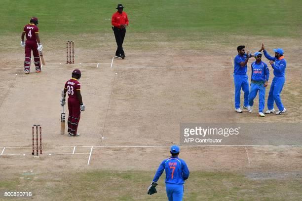 India's Bhuvneshwar Kumar celebrates with teammate India's Ajinkya Rahane and captain Virat Kohli after dismissing West Indies' Jason Mohammed during...