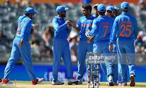 India's Bhuvneshwar Kumar celebrates with teammates after taking the wicket of United Arab Emirates batsmen Amjad Ali during the 2015 Cricket World...