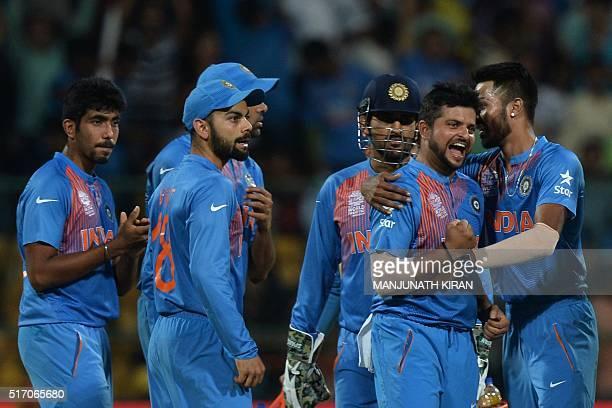 India's bowler Suresh Rainacelebrates with teammates after taking the wicket of Bangladesh batsman Sabbir Rahman during the World T20 cricket...