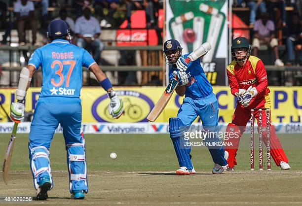 India's captain Ajinkya Rahane bats as Zimbabwe's wicket keeper Charles Coventry looks on during the first of two Twenty20 international cricket...
