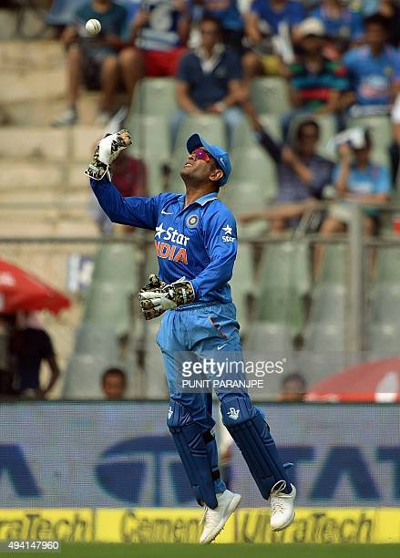 India's captain and wicketkeeper Mahendra Singh Dhoni celebrates after taking the catch to dismiss South Africa's Hashim Amla during the fifth one...