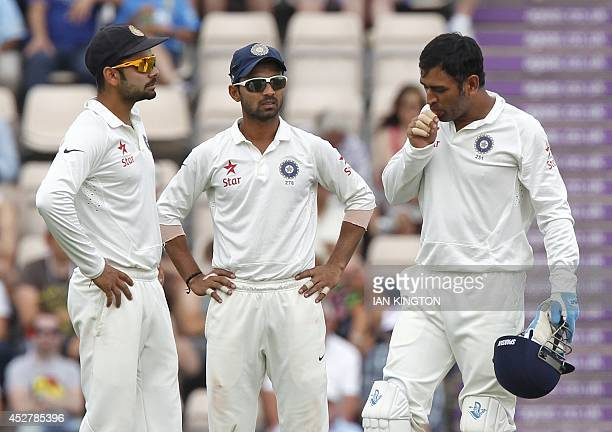India's Captain and wicketkeeper Mahendra Singh Dhoni reacts after hurting his finger as teammates Ajinkya Rahane and Virat Kohli look on during the...